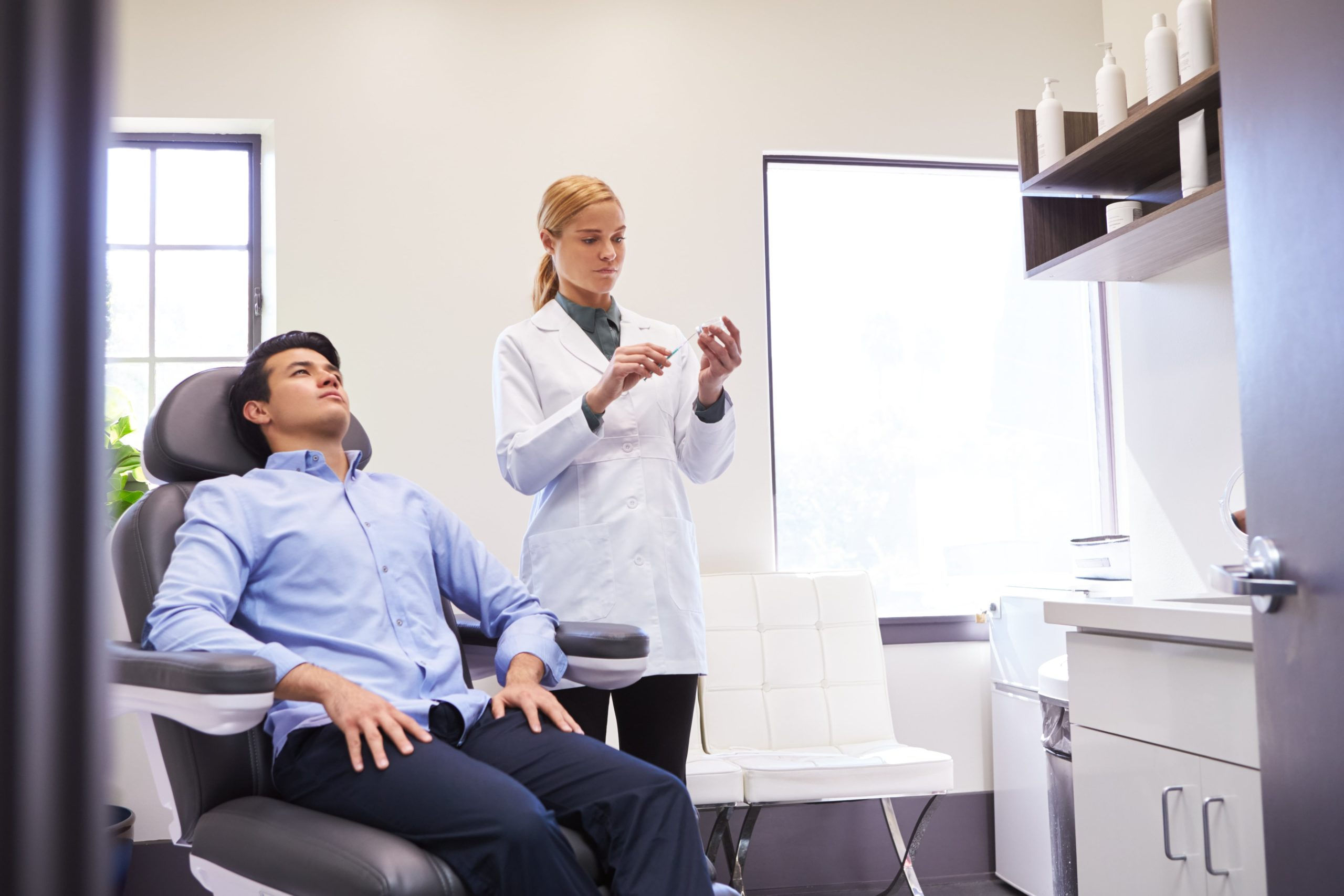 man sitting in chair being give botox injection