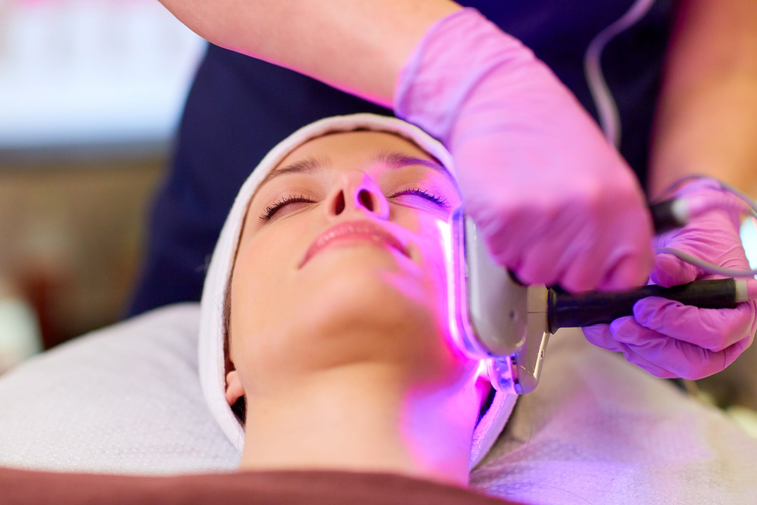 Beautician with Diamond Microdermabrasion device doing face exfoliation to young woman lying at spa