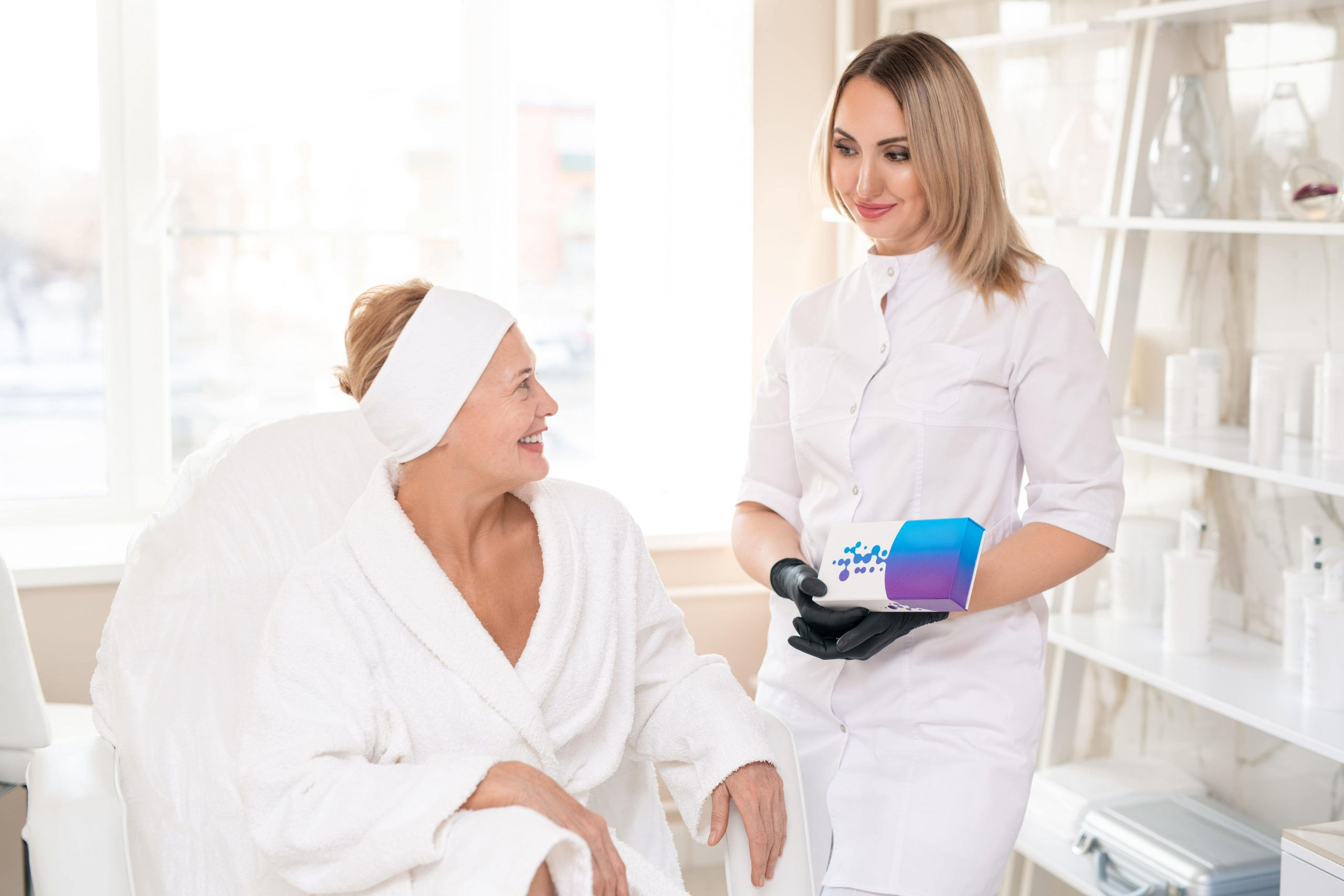 Young cosmetologist in white coat talking to mature client and presenting new filler to her at skin treatment procedure